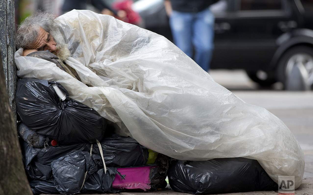 In this Oct. 3, 2016 photo, a homeless man sleeps on top of his belongings on the sidewalk, early in the morning in Buenos Aires, Argentina. The president of the World Bank recently praised President Mauricio Macri's efforts at providing clear data as a crucial step to reduce poverty. (AP Photo/Natacha Pisarenko)