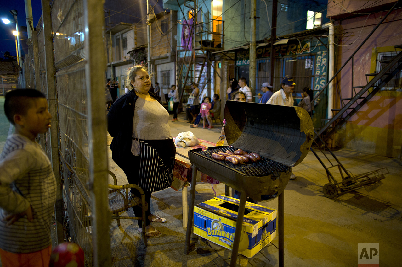 """In this Oct. 13, 2016 photo, Miriam Cruz, center, cooks chorizos for meat sandwiches called """"choripanes"""" in the Villa 3 neighborhood of Buenos Aires, Argentina. Since her husband lost his job four months ago, Cruz has been the only breadwinner in her family of four, and her two daughters line up every night outside the soup kitchen because they can no longer afford dinner. (AP Photo/Natacha Pisarenko)"""