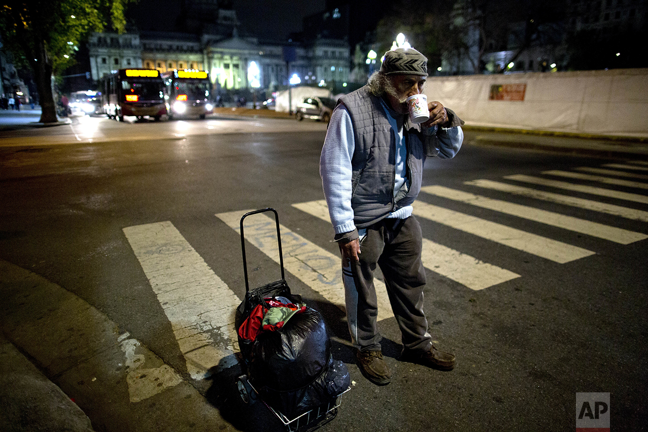 In this Oct. 5, 2016 photo, a homeless man drinks tea, given to him by a soup kitchen volunteer, in Buenos Aires, Argentina. The governments that took power since 2003 focused on rescuing Argentina from a devastating 2001 economic crisis that left one of every five Argentines out of work while some reported going hungry. Many economists are urging current President Mauricio Macri to continue his reforms, even if they are painful for now. (AP Photo/Natacha Pisarenko)