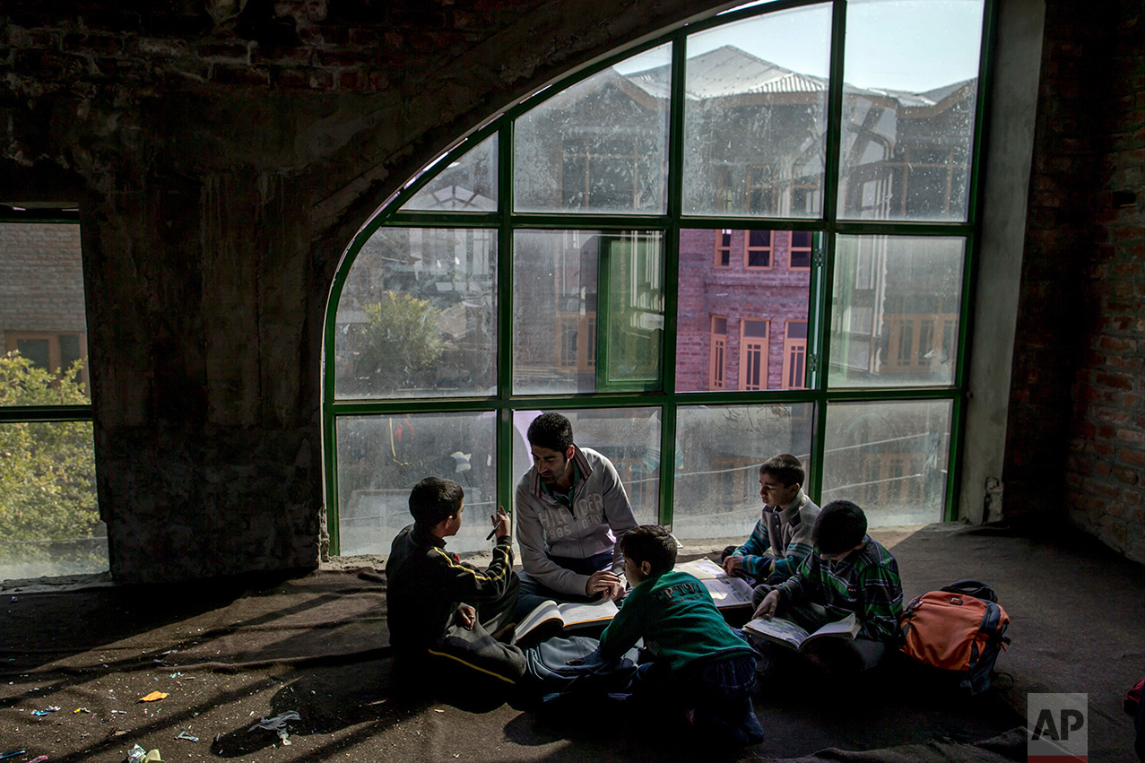 In this Thursday, Oct. 20, 2016 photo, Faheel Abbas teaches Kashmiri children in an ad-hoc learning center at a local mosque in Srinagar, Indian controlled Kashmir. With daily life still paralyzed by strikes and rolling curfews, dozens of learning centers have popped up in people's homes or religious centers like mosques in Kashmir since August. They gather during daylight hours, often sitting on the floor, to hear a teacher read aloud from a text or practice mathematical equations in a shared notebook. (AP Photo/Dar Yasin)