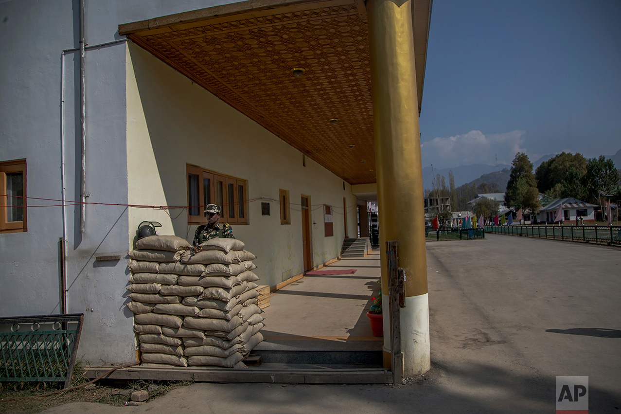 In this Friday, Oct. 21, 2016 photo, a paramilitary soldier keeps vigil inside the Government Girls Higher Secondary Institute after it was converted into a paramilitary bunker in Srinagar, Indian controlled Kashmir. Kashmir has been under a tight security lockdown, along with a separatist-sponsored strike, as Indian forces struggle to quell the uprising and arrest thousands of civilian protesters. The region, also claimed by Pakistan, is divided between the two nuclear-armed neighbors by a heavily militarized Line of Control. (AP Photo/Dar Yasin)