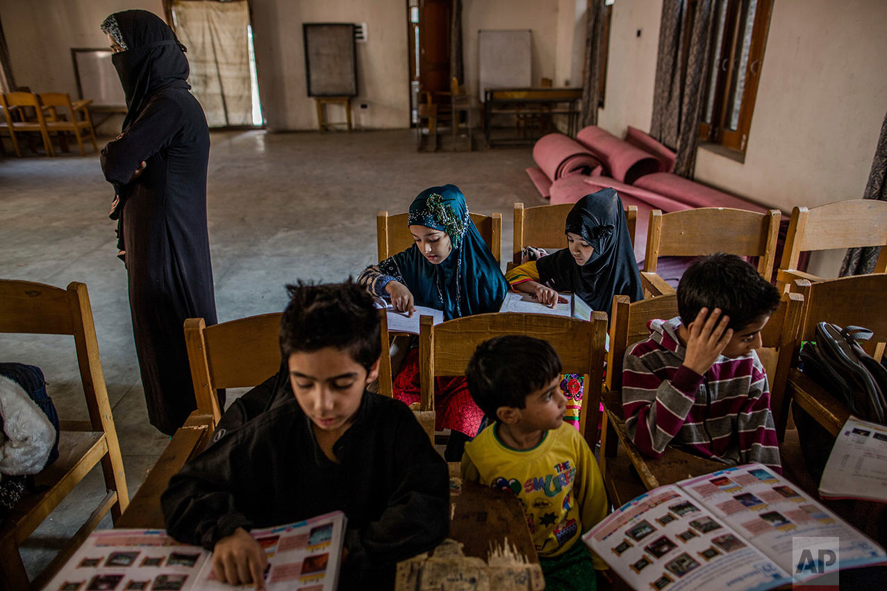 In this Friday, Oct. 7, 2016 photo, Kashmiri children attend an ad-hoc learning center set up in a community marriage hall in Srinagar, Indian controlled Kashmir. With daily life still paralyzed by strikes and rolling curfews, dozens of learning centers have popped up in people's homes or religious centers like mosques in Kashmir since August. The centers are doing more than just helping students prepare for upcoming exams, organizers said. They're keeping kids off the streets and giving them comfort amid a civilian uprising sparked when a popular rebel leader was killed in fighting Indian forces on July 8. (AP Photo/Dar Yasin)