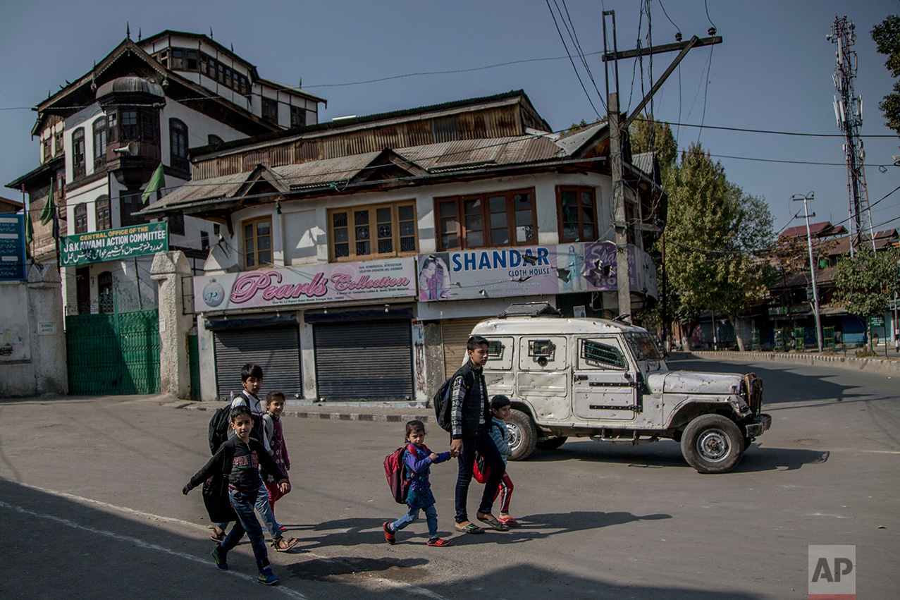 In this Friday, Oct. 21, 2016 photo, Kashmiri children walk home after attending private classes, on a deserted street during curfew in Srinagar, Indian controlled Kashmir. With daily life still paralyzed by strikes and rolling curfews, dozens of ad-hoc learning centers have popped up in people's homes or religious centers like mosques in Kashmir since August. (AP Photo/Dar Yasin)