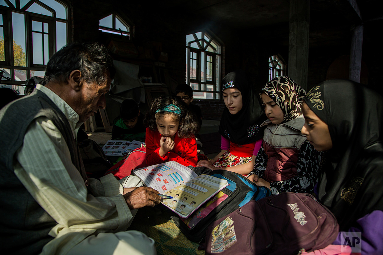 In this Thursday, Oct. 20, 2016 photo, Mohammad Hussain teaches Kashmiri children at an ad-hoc learning center at a local mosque in Srinagar, Indian controlled Kashmir. With daily life still paralyzed by strikes and rolling curfews, dozens of learning centers have popped up in people's homes or religious centers like mosques in Kashmir since August. The centers are doing more than just helping students prepare for upcoming exams, organizers said. They're keeping kids off the streets and giving them comfort amid a civilian uprising sparked when a popular rebel leader was killed in fighting Indian forces on July 8. (AP Photo/Dar Yasin)