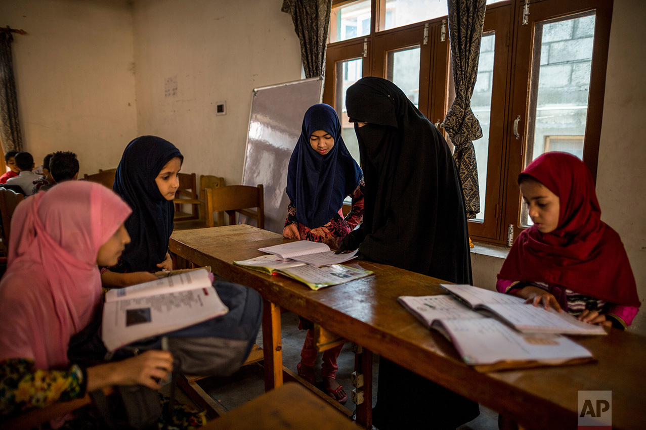 In this Friday, Oct. 7, 2016 photo, Kashmiri girls study in an ad-hoc learning center set up in a community marriage hall in Srinagar, Indian controlled Kashmir. With daily life still paralyzed by strikes and rolling curfews, dozens of learning centers have popped up in people's homes or religious centers like mosques in Kashmir since August. The centers are doing more than just helping students prepare for upcoming exams, organizers said. They're keeping kids off the streets and giving them comfort amid a civilian uprising sparked when a popular rebel leader was killed in fighting Indian forces on July 8. (AP Photo/Dar Yasin)