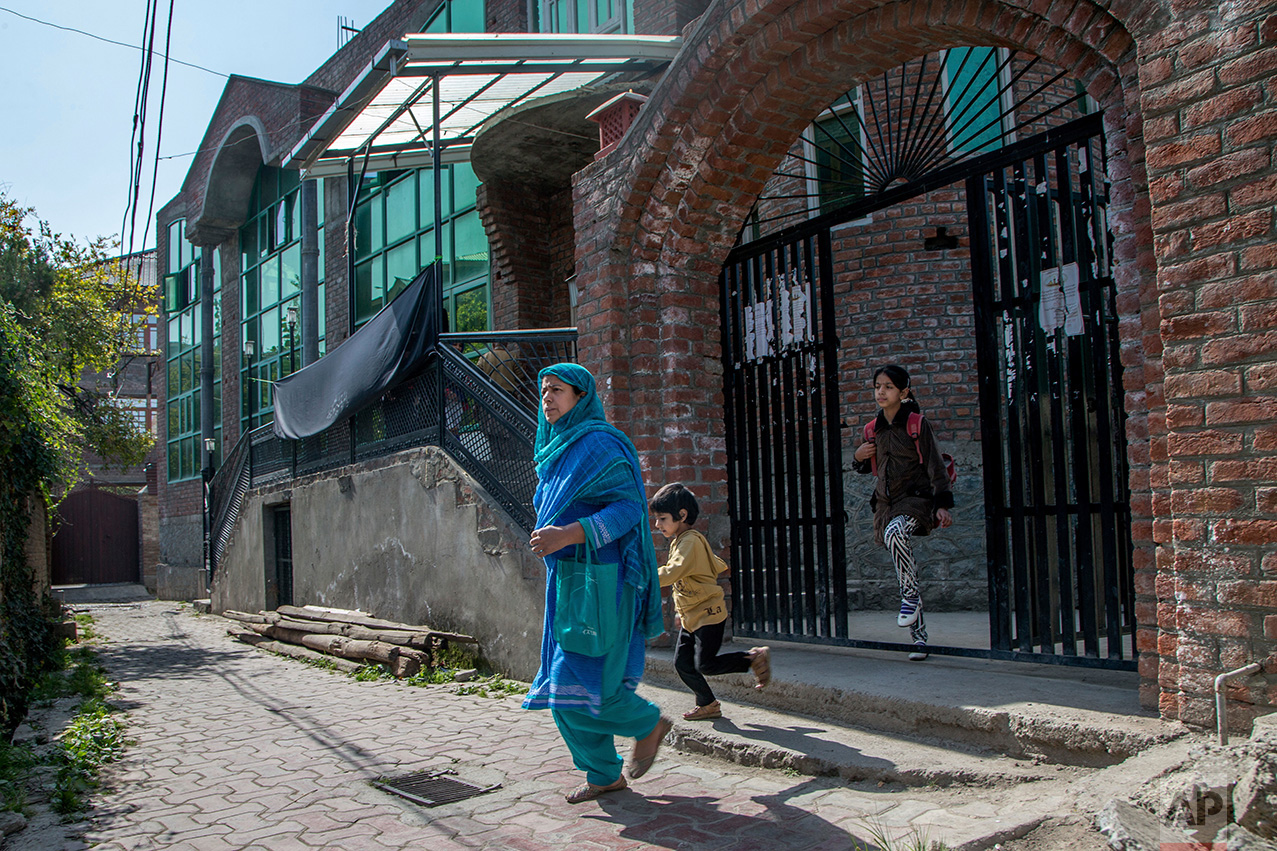 In this Thursday, Oct. 20, 2016 photo, a Kashmiri woman walks home with her children after attending alternate classes set up at a local mosque in Srinagar, Indian controlled Kashmir. With daily life still paralyzed by strikes and rolling curfews, dozens of ad-hoc learning centers have popped up in people's homes or religious centers like mosques in Kashmir since August. The centers are doing more than just helping students prepare for upcoming exams, organizers said. They're keeping kids off the streets and giving them comfort amid a civilian uprising sparked when a popular rebel leader was killed in fighting Indian forces on July 8. (AP Photo/Dar Yasin)