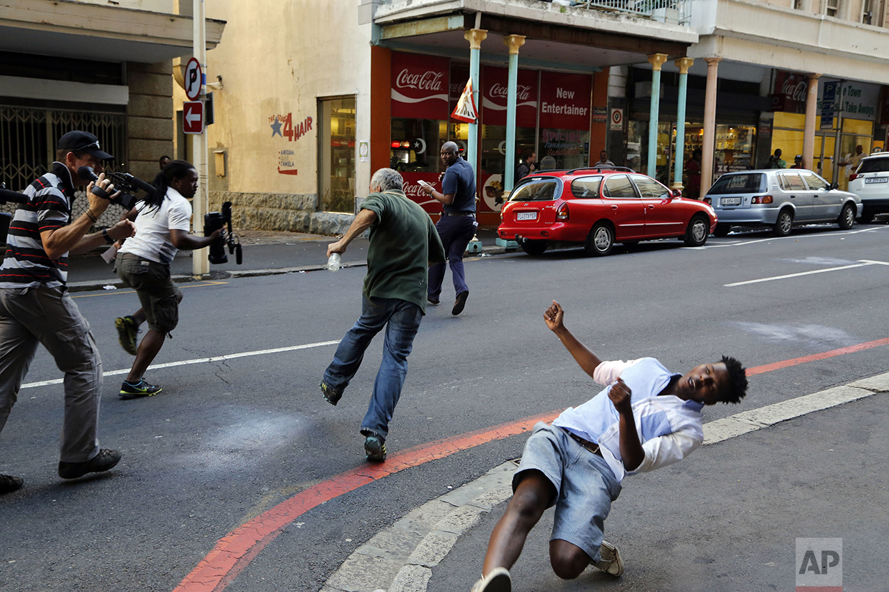 A student protestor, right, is hit by a rock thrown by a fellow protestor in Cape Town, South Africa, Wednesday, Oct. 26, 2016. South African police have used stun grenades to disperse student protesters outside parliament, where the finance minister was giving a budget speech. Protests for free education have hit many South African campuses since the previous month, when the government recommended that universities increase 2017 fees by no more than 8 percent. It also promised to cover fee increases for poor students. (AP Photo/Schalk van Zuydam)