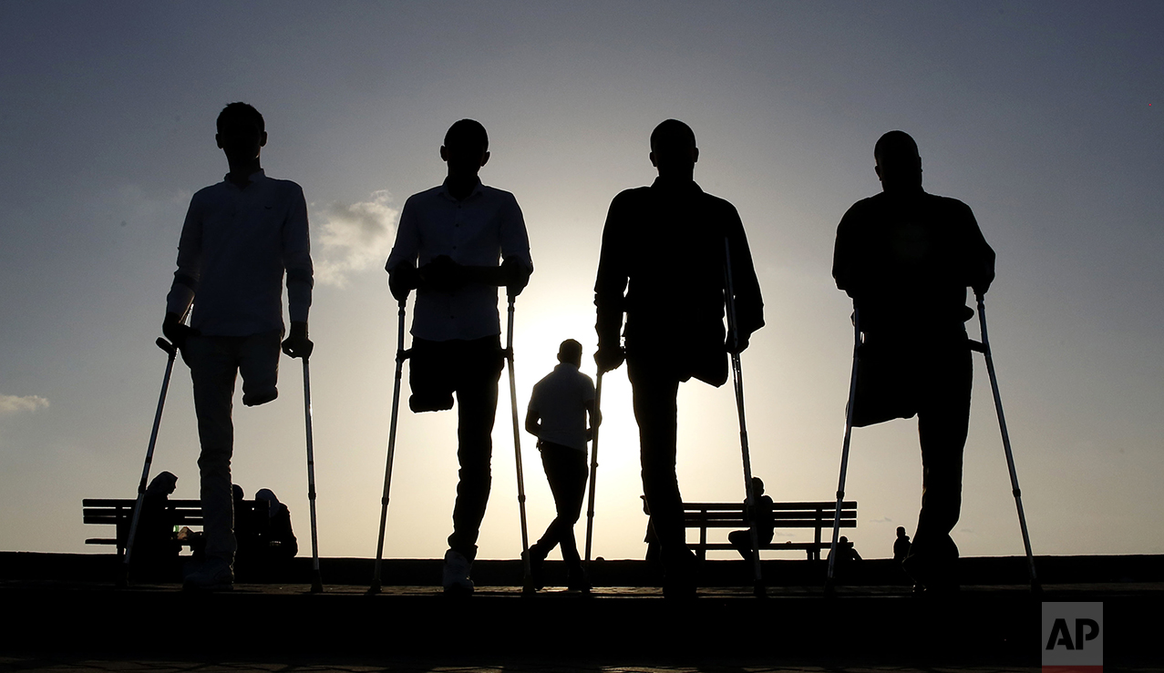 Four Palestinian friends who were injured during conflicts stand together by the sea at Gaza's small fishing harbor, Monday, Oct. 24, 2016. Fighting has left thousands of people with disabilities in this Palestinian enclave. (AP Photo/Hatem Moussa)