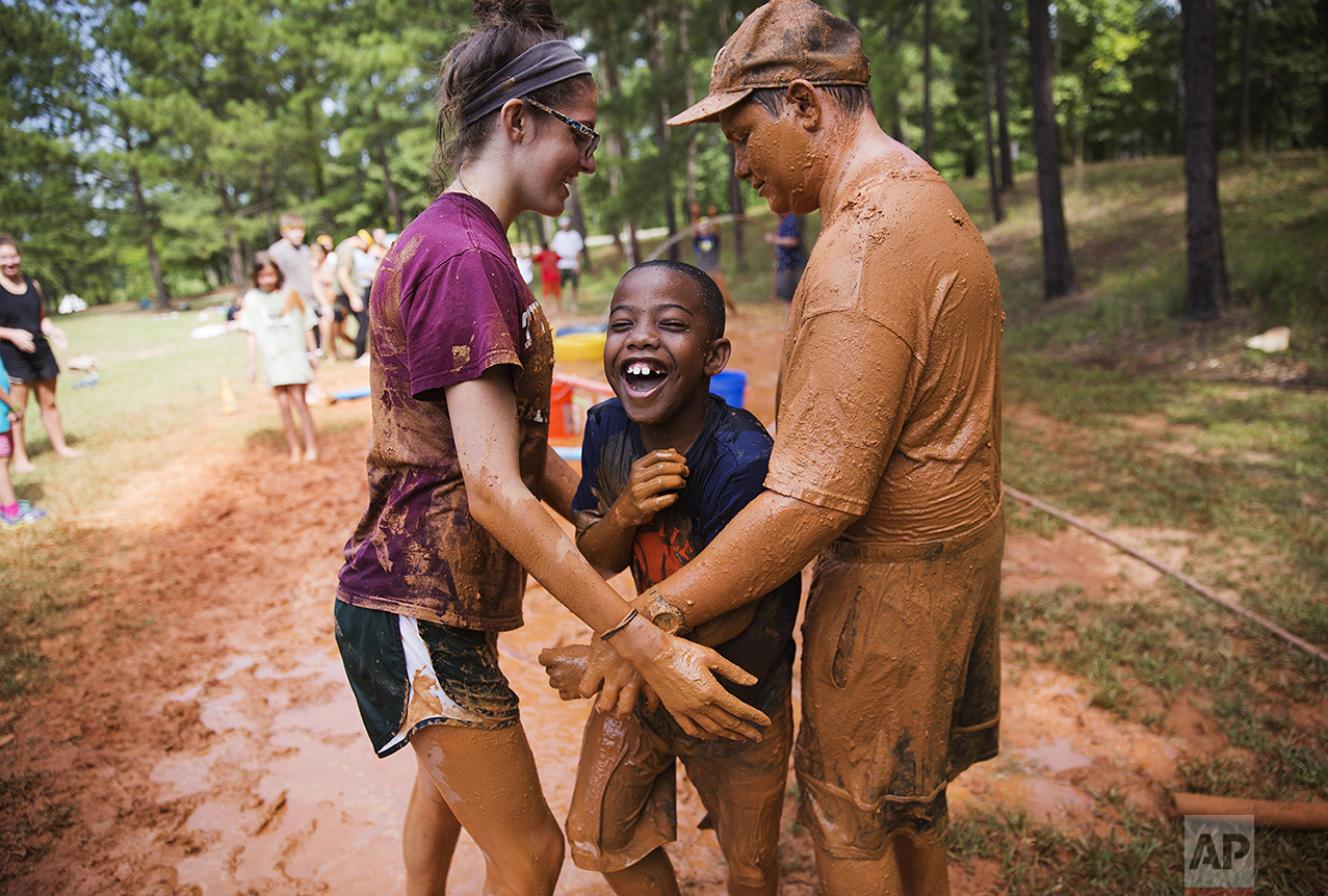 In this Thursday, July 17, 2014 photo, camper Jacob Threatt, 9, of Macon, Ga., center, is hugged by counselors in training Savannah Sherman, 16, left, and Drew Donovan, 17, while running through a mud obstacle course at Camp Twitch and Shout, a camp for children with Tourette's Syndrome in Winder, Ga. (AP Photo/David Goldman)
