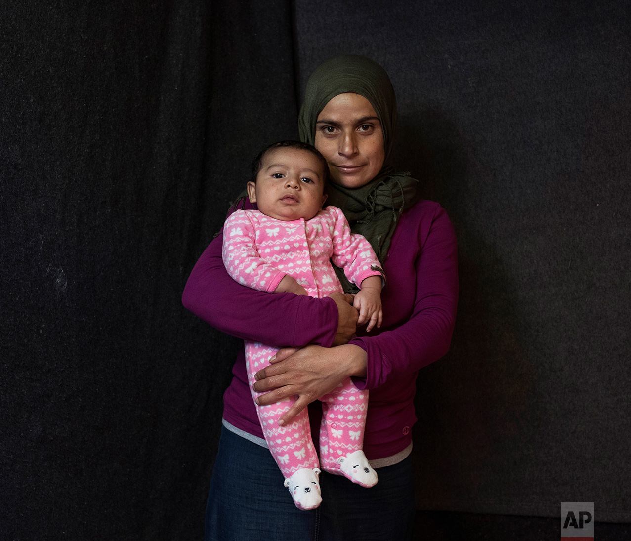 In this Wednesday Oct. 19, 2016, 25-year-old Arna Al Mousa, a Syrian mother from the city of Idlib, poses with her baby boy Yousef Al Mousa in a tent made of blankets given by the UNCHR at the Ritsona refugee camp in Greece. Anna is one of the hundreds of refugee women who gave birth while stranded in Greece. Yousef, the family's fourth child, was born on Wednesday, Aug. 17, 2016 in the hospital of the nearby town of Chalkida. (AP Photo/Petros Giannakouris)