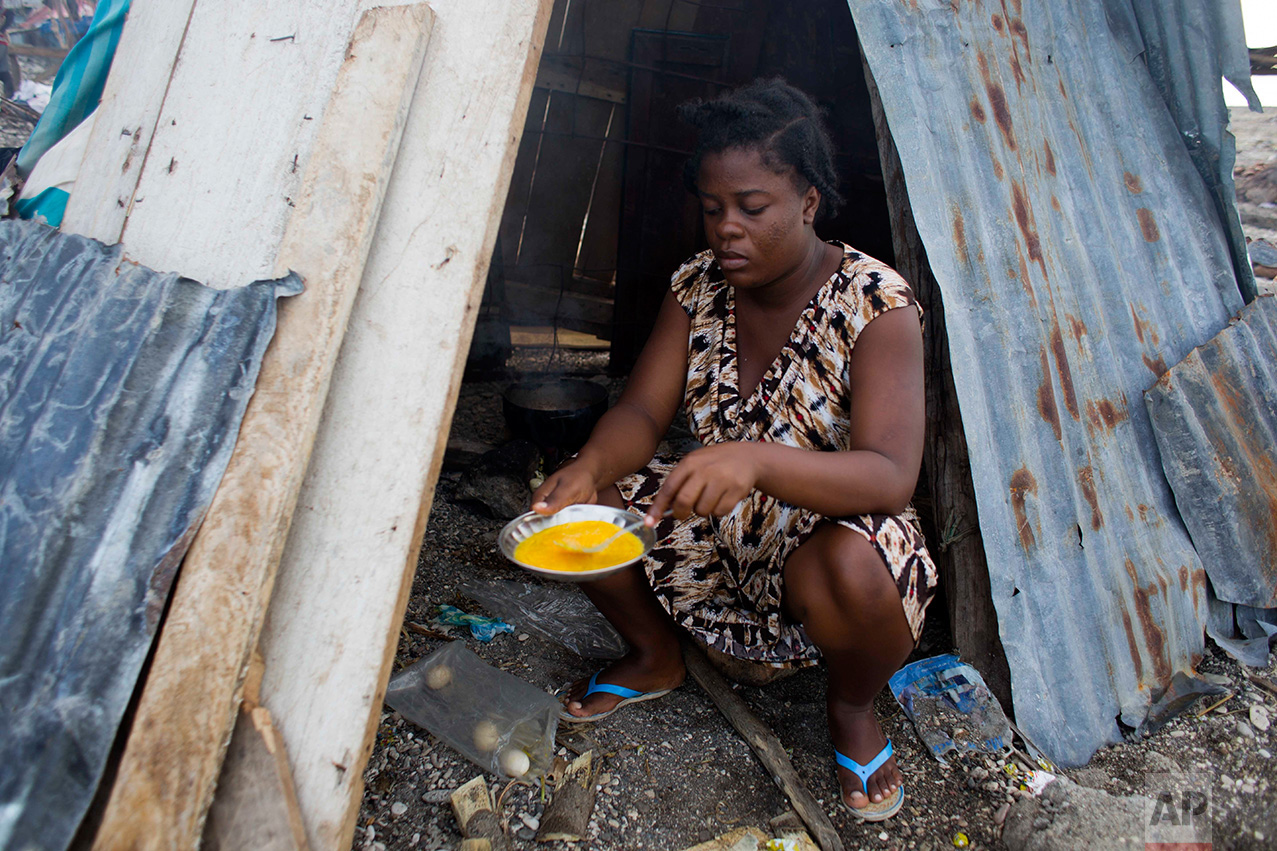 In this Nov. 1, 2016 photo, 19-year-old Nathanaelle Bernard, who is 7 months pregnant, cooks an omelet in a makeshift hut she is sharing with five members of her extended family, in Coteaux, Haiti. Hurricane Matthew destroyed her small home of cinder blocks and carried away most of her belongings, including the clothing and blankets she had managed to collect for her baby. (AP Photo/Dieu Nalio Chery)