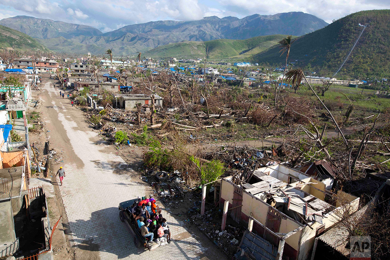 "In this Nov. 1, 2016 photo, vendors are transported in a ""tap-tap"" past a landscape of destruction, caused by Hurricane Matthew, in Coteaux, Haiti. Many experts fear the advances Haiti made, have been rolled back by the storm, which made landfall on the peninsula on Oct. 4, with 145 mph winds. (AP Photo/Dieu Nalio Chery)"