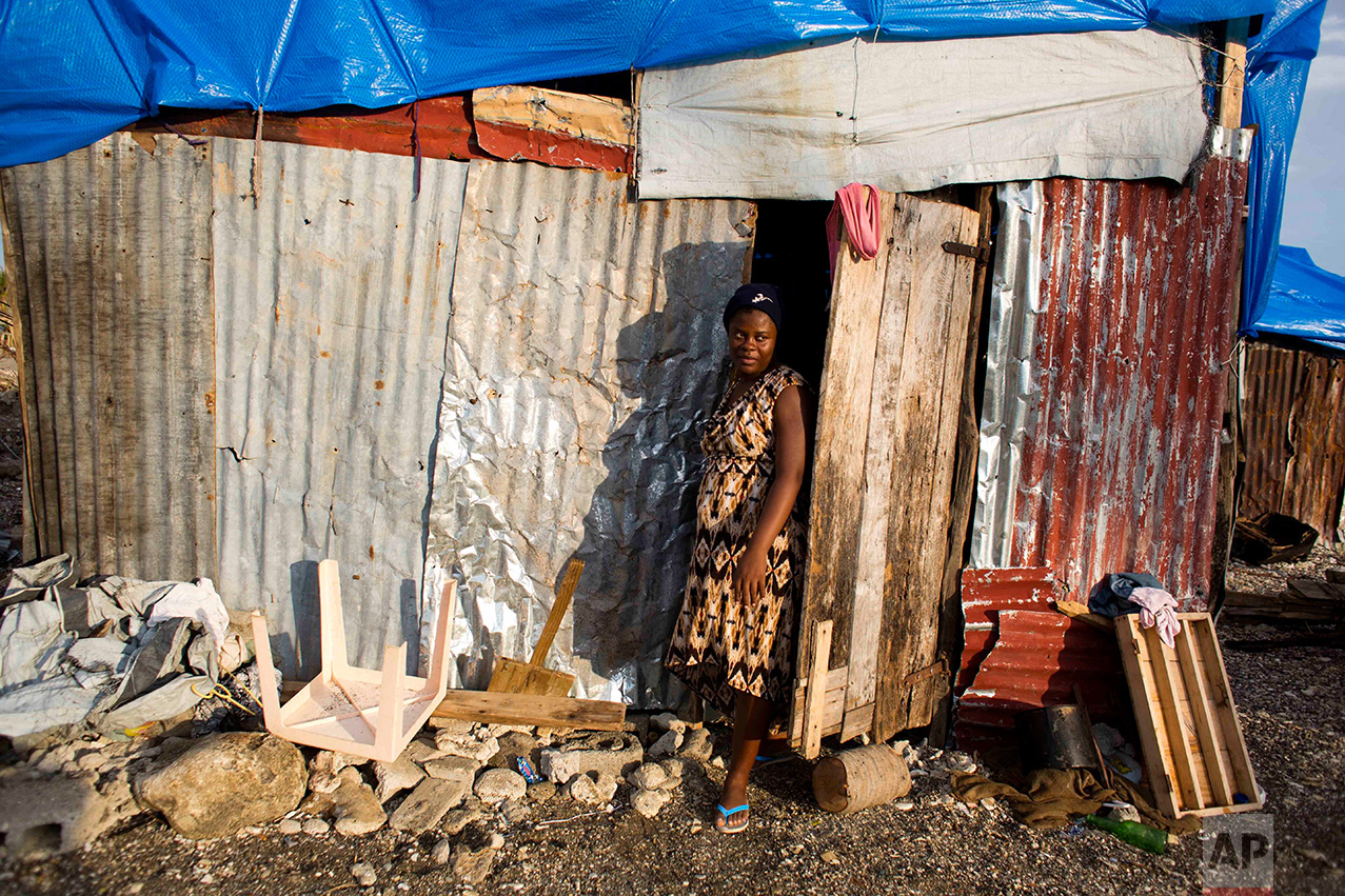 In this Oct. 31, 2016 photo, Nathanaelle Bernard, who is 7 months pregnant, steps outside from a makeshift hut where she now lives, after her home was destroyed by Hurricane Matthew, in Coteaux, Haiti. The 19-year-old is among the nearly 14,000 women who are due to give birth in the coming weeks amid widespread shortages of food, water and housing. (AP Photo/Dieu Nalio Chery)