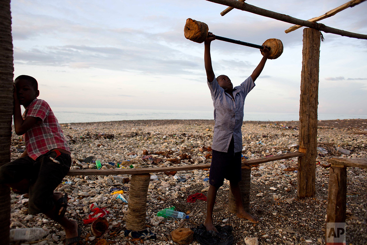 "In this Nov. 1, 2016 photo, a boy lifts makeshift barbells near his home, destroyed by Hurricane Matthew, in Coteaux, Haiti. ""It is tragic that a single storm can tear up so much of this progress, and that in a single day we can be set back by years,"" said Marielle Sander, representative for the U.N. Population Fund in Haiti. (AP Photo/Dieu Nalio Chery)"