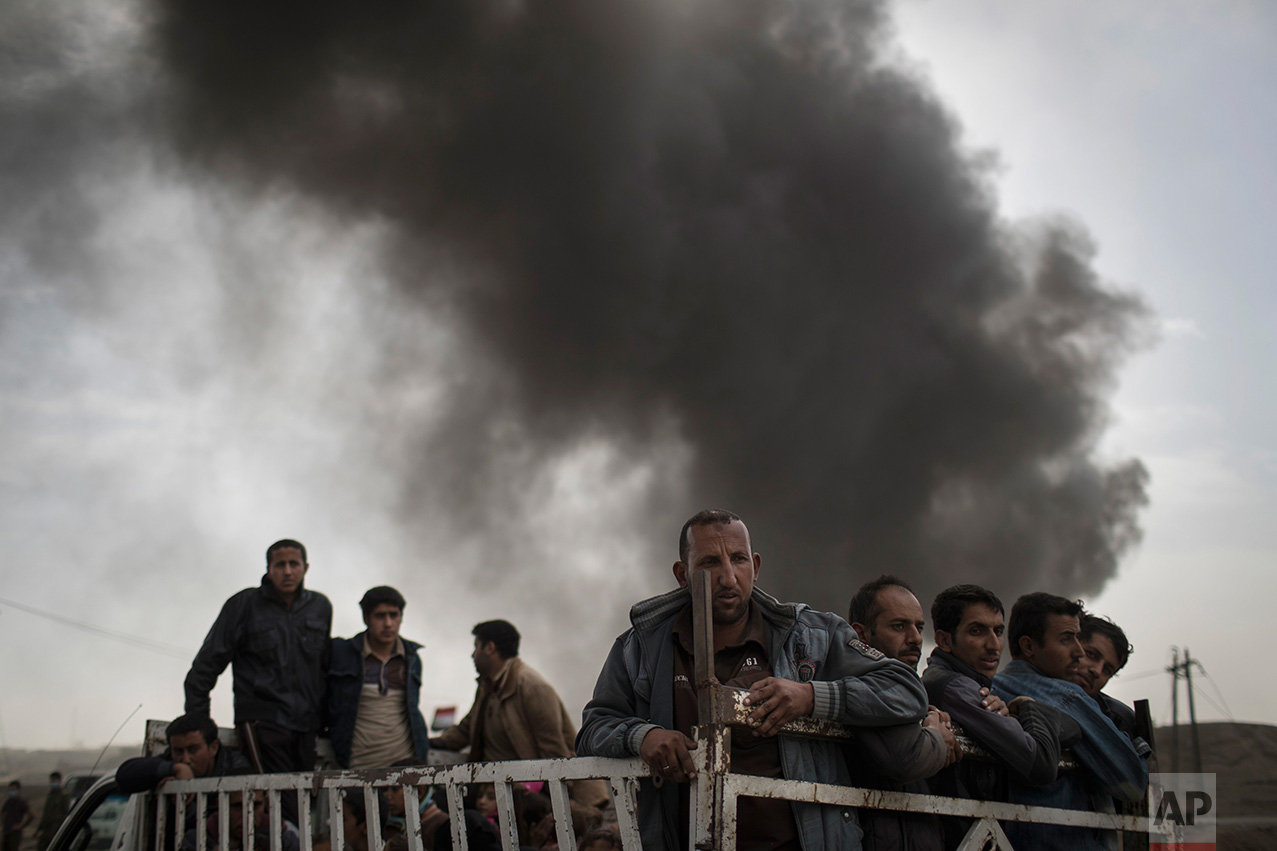 Displaced people stand on the back of a truck at a checkpoint near Qayara, south of Mosul, Iraq, Tuesday, Nov. 1, 2016. The UN human rights office is lauding efforts by the U.S.-led coalition in the battle against the Islamic State group in Mosul. The office in Geneva says coalition flights over Iraq have largely succeeded in preventing IS from bringing in 25,000 more civilians to the city center, where the militant group has been using people as human shields as Iraqi forces advance on Mosul. (AP Photo/Felipe Dana)
