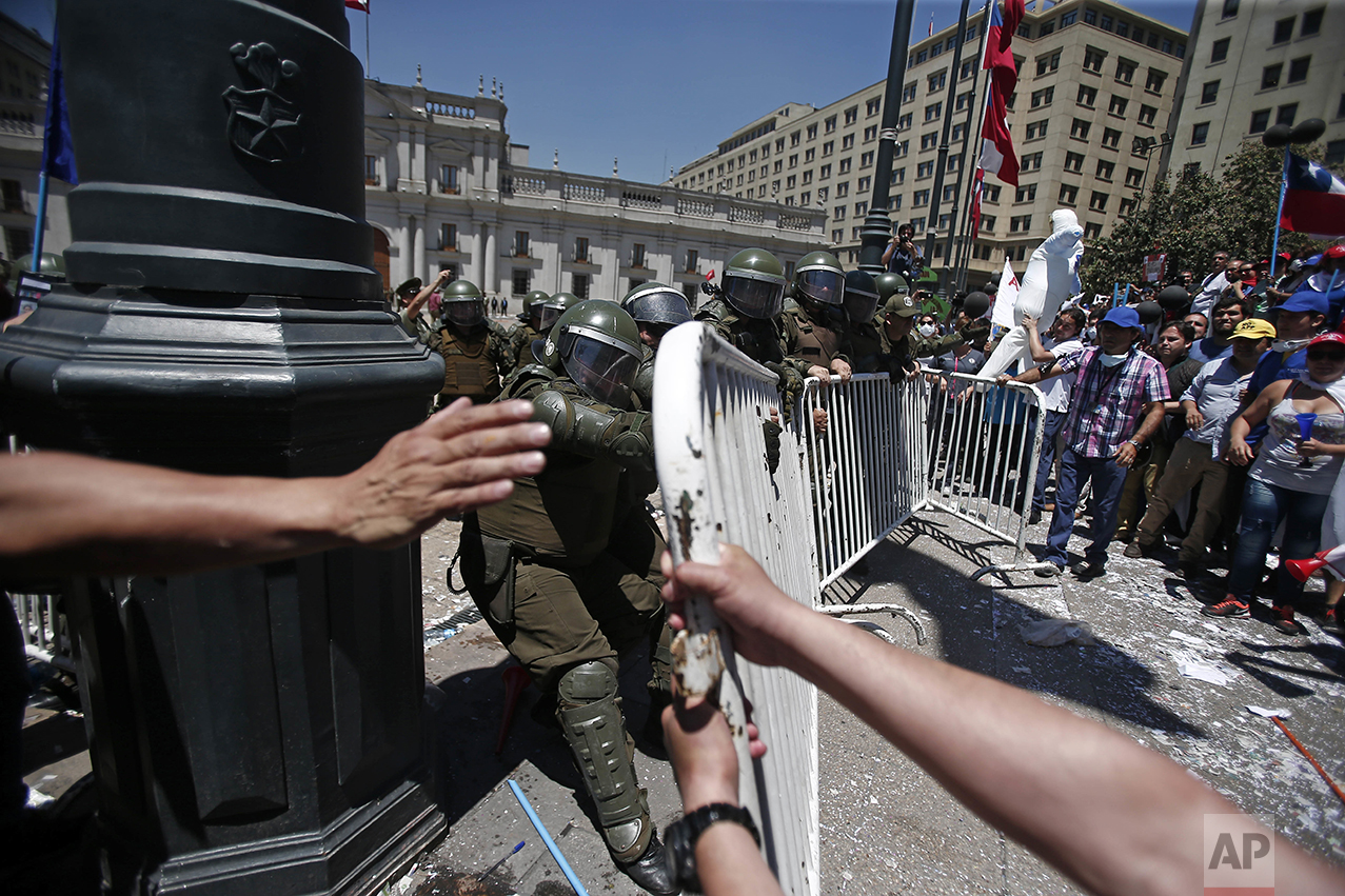 Public workers try to break past a police barrier to reach La Moneda presidential palace in Santiago, Chile, Thursday, Nov. 17, 2016. Workers upset with their salary increase, 3.2 percent approved Wednesday by Congress, want a 4 percent increase, after lowering their demand from 7 percent. (AP Photo/Luis Hidalgo)