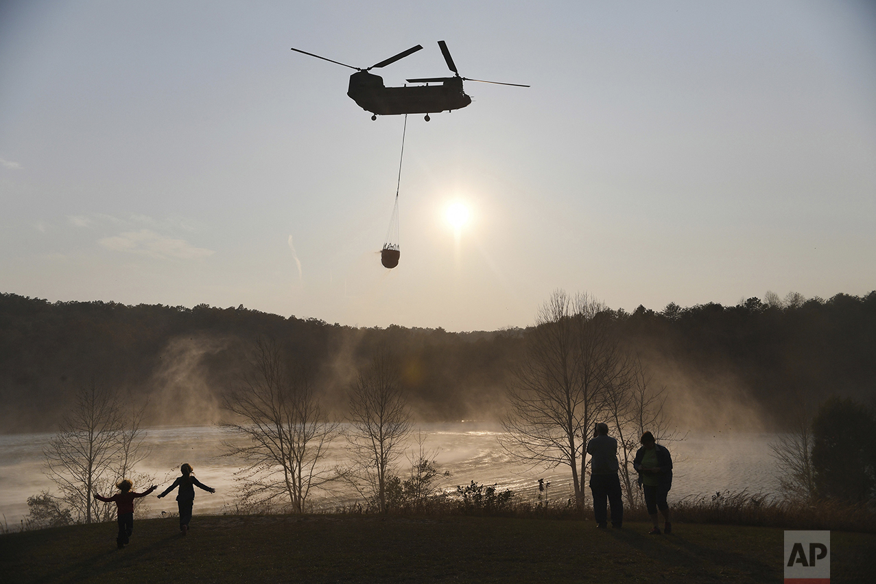 A Chinook helicopter pulls water out of Lake Oolenoy near Table Rock State Park in S.C., as firefighters continue to battle wildfires on Tuesday, Nov. 15, 2016. Dozens of wildfires have burned hundreds of square miles across the Southeast of the U.S. and thrown a shroud of smoke over the region. (Heidi Heilbrunn/The Greenville News via AP)