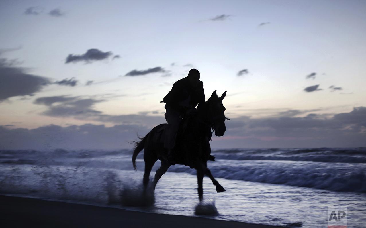 A Palestinian man rides a horse on the beach as the sun sets over Gaza City, Thursday, Nov. 17, 2016. (AP Photo/ Khalil Hamra)