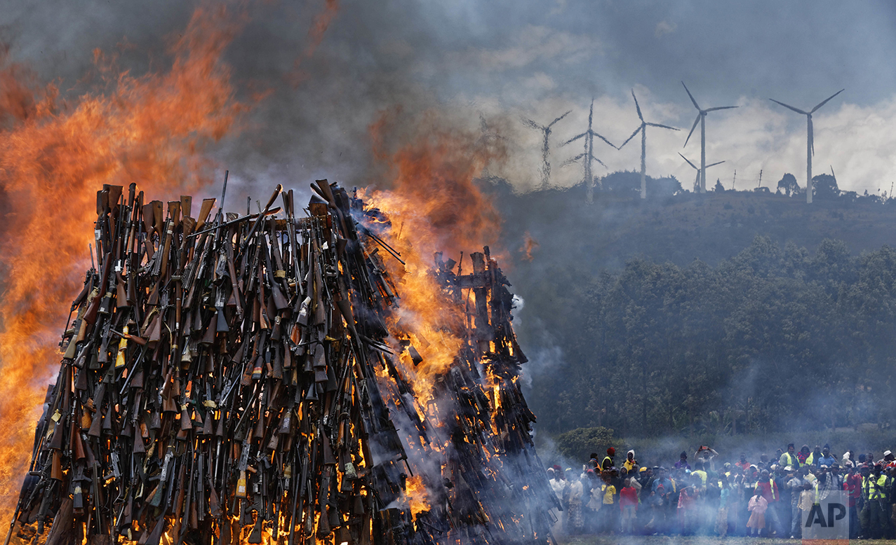 A pile of over 5,000 illegal weapons are burned by Kenyan police in Ngong, near Nairobi, in Kenya Tuesday, Nov. 15, 2016. The weapons consisted of both confiscated and surrendered firearms that had been stockpiled over almost a decade and were destroyed by police as a message to the public to surrender others. (AP Photo/Ben Curtis)