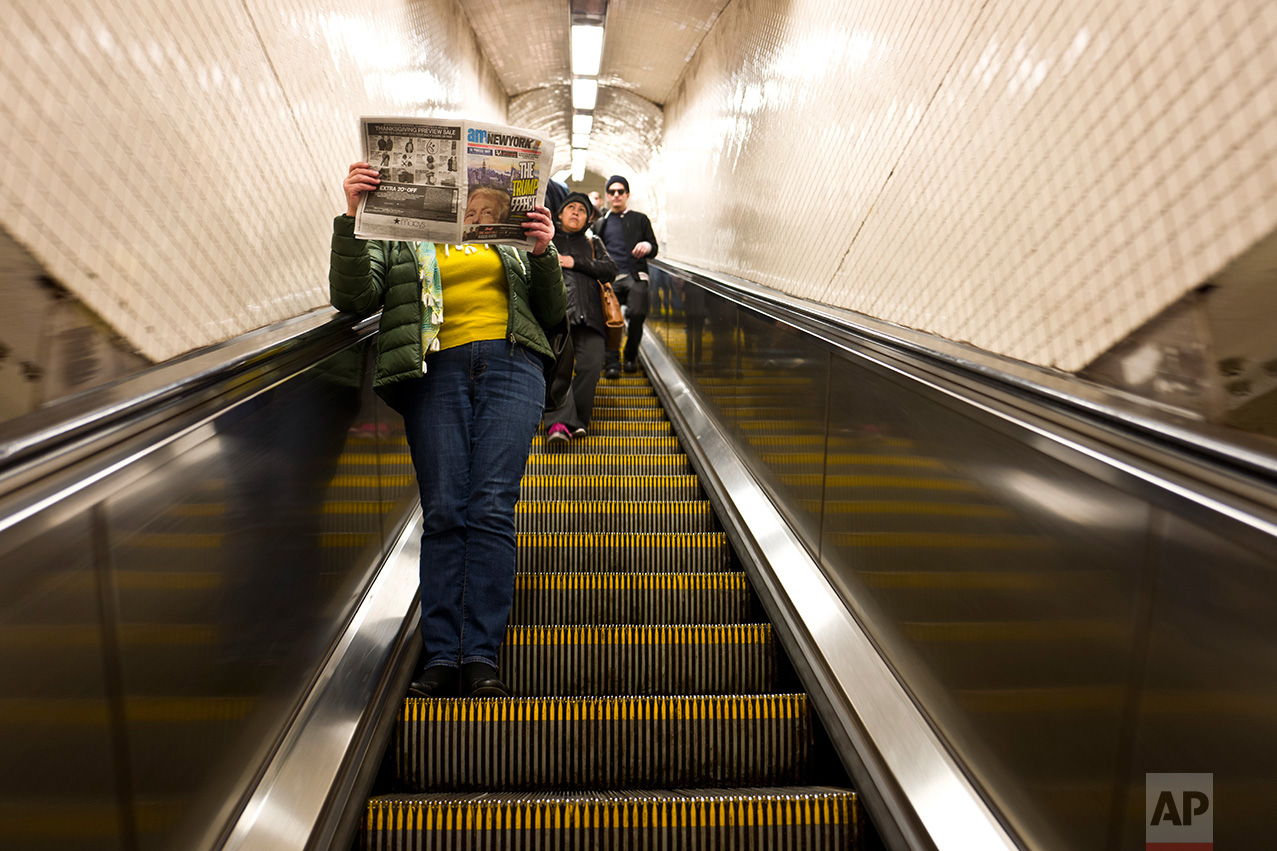 In this Monday, Nov. 14, 2016 photo, a woman reads a newspaper featuring on its front page an image of President-elect Donald Trump while going down an escalator of a subway station in New York. (AP Photo/Muhammed Muheisen)