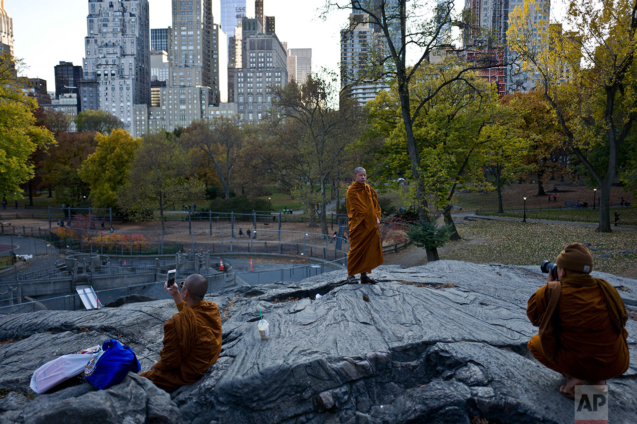 In this Thursday, Nov. 17, 2016 photo, a monk poses for a picture taken by another monk at Central Park in New York. (AP Photo/Muhammed Muheisen)
