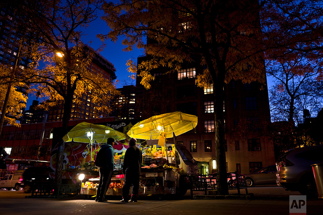 In this Thursday, Nov. 17, 2016 photo, a fruits and vegetables vendor, right, talks with a man while waiting for customers next to his stall on a roadside in New York. (AP Photo/Muhammed Muheisen)