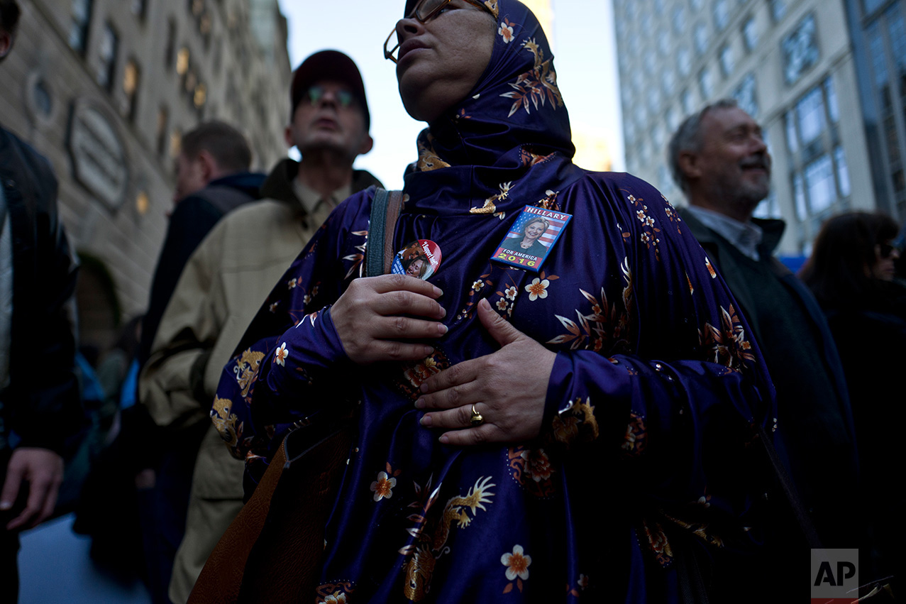 In this Sunday, Nov. 13, 2016 photo, a protestor wearing pins of support for Democratic presidential candidate Hillary Clinton, stands outside Trump Tower while she and others take part in a march against President-elect Donald Trump in New York. (AP Photo/Muhammed Muheisen)