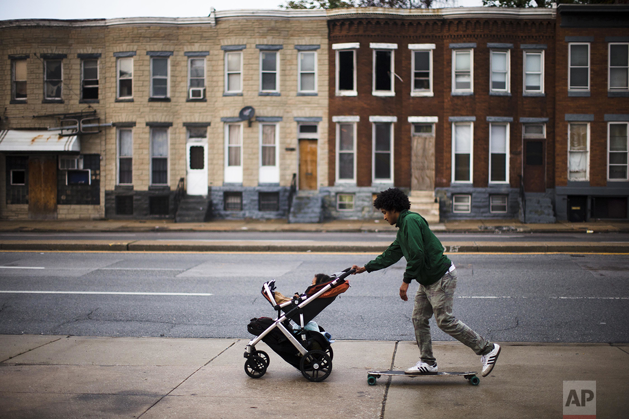 "Carde Cornish, rides a skateboard as he takes his son, also named Carde, home past blighted buildings in Baltimore on Wednesday, May 11, 2016. Cornish, a young man who has spent his entire life in and around the Baltimore neighborhood where Freddie Gray lived and died, is socially and politicly engaged with the city around him. He works for Taharka Brothers, an ice-cream company with a social mission. ""Our race issues aren't necessarily toward individuals who are white, but it is towards the system that keeps us all down, one, but keeps black people disproportionally down a lot more than anybody else,"" says Cornish. (AP Photo/Matt Rourke)"