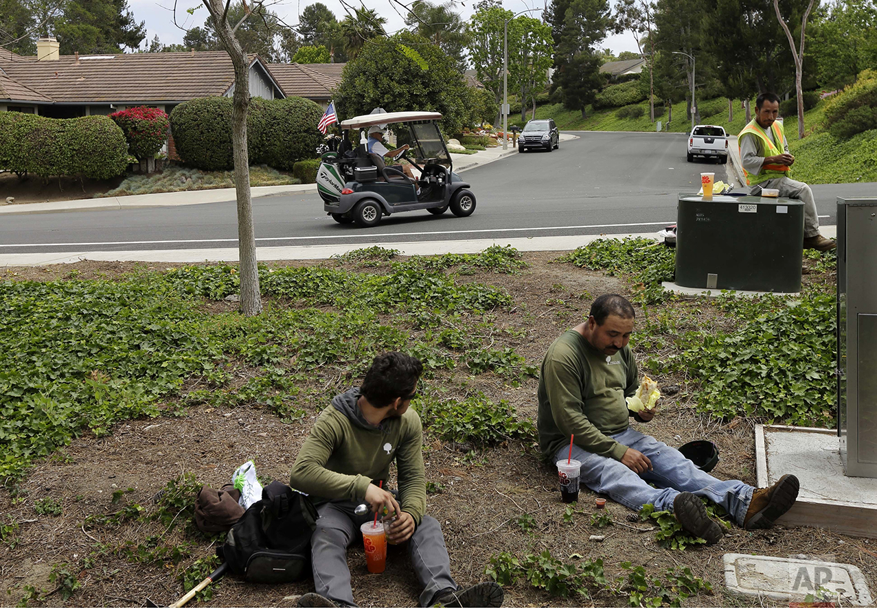 "Duncan Wallace drives a golf cart from his house to his golf club as a group of landscape workers take a break in Vista, Calif., on Wednesday, May 4, 2016. Wallace, who owns a medical supplies company, said he's been a conservative for 50 years, ever since he read Barry Goldwater's book, ""Conscience of a Conservative."" ""I think we punish success, actually,"" he says. ""I know a lot of people who are quite successful, and they are paying an awful lot of money in taxes. They are paying for people who don""t have their oar in the water."" (AP Photo/Gregory Bull)"