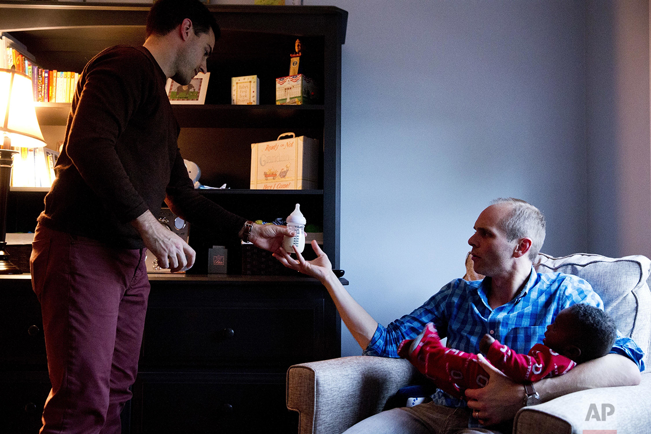 "Brooks Brunson, left, passes a bottle of formula to his husband, Gregg Pitts, as they prepare their son, Thomas Brunson-Pitts, 6-months old, for bed at their home in Washington on Wednesday, May 4, 2016. Originally from Texas and Ohio, they were married in the District of Columbia in November 2013. Brunson and Pitts always knew they wanted to have a family together, and were delighted when they were able to start the adoption process for their son shortly after beginning to look for a match in 2015. Although it's an open adoption, the mother has chosen not to be involved in her child's life and had no problem with a same sex couple adopting her son. ""We're an interracial same sex couple family,"" says Brunson, ""But our day-to-day life is picking up dry cleaning, getting to work on time, making sure Thomas has his bottle prepared - we're the most boring people I know. But then when I take a step back I realize we are very unique. But I believe this is exactly where God wants me to be."" The District of Columbia legalized gay marriage in 2010. (AP Photo/Jacquelyn Martin)"