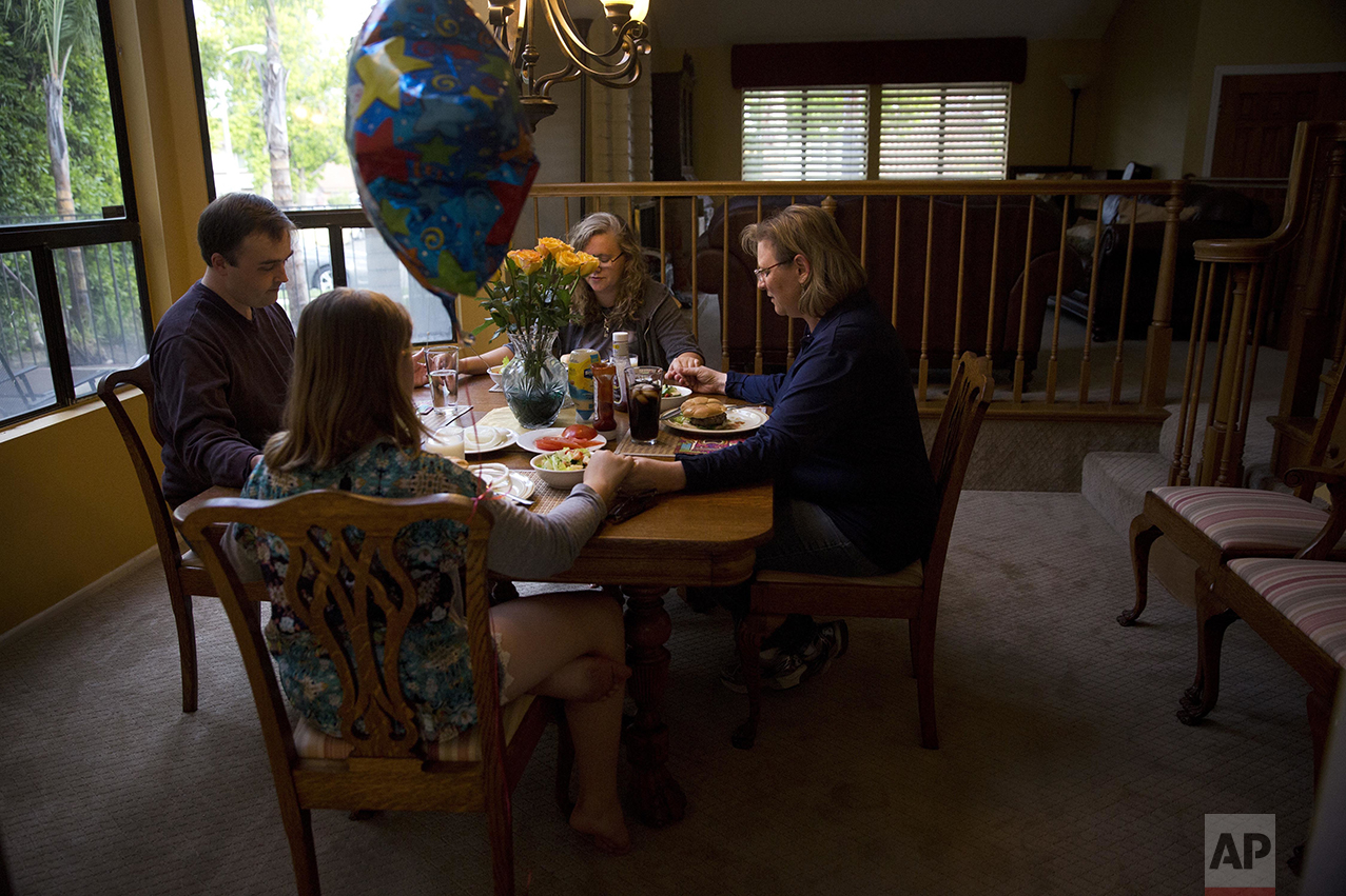 "Karen Fagan, right, and husband, Ian, hold hands with Karen's two daughters, Kate and Elizabeth Bowman as they pray to celebrate Elizabeth's birthday in Upland, Calif., on Saturday, May 7, 2016. Fagan's ex-husband, Harry Bowman, the father of her two daughters, was killed in the previous year's terrorist attack in San Bernardino, Calif. But the tragic event didn't change her beliefs, and she began participating in interfaith community events. Fagan still thinks that the county should accept Muslim refugees. ""America is full of lots of different people from lots of different places,"" said Fagan. ""It saddens me that America is no longer the place where people can come to escape oppression... It's our obligation as Americans and Christians."" (AP Photo/Jae C. Hong)"
