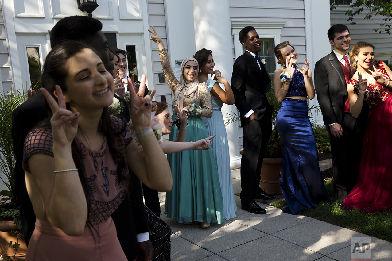 "Hannah Shraim, center left, poses with Ashley Riddle, center right, as their group for the Northwest High School senior prom prepares for a ""fun"" photograph for their parents in Germantown, Md., on Friday, May 13, 2016. Shraim and Riddle both went to prom solo while others in the group brought dates. Senior class president and an observant Muslim, Shraim prays five times a day and hopes to become an advocate for Muslims in the United States. Since 10th grade she has worn the Islamic headscarf as part of her personal faith. It was a decision her parents were concerned about, even discouraging due to their fears of how their daughter might be treated by strangers. ""If Trump becomes the president then not just Muslims but a lot of people will live in fear of the future for themselves and their children, given the scapegoating technique of pushing out minorities rather than focusing on how we can benefit everyone."" (AP Photo/Jacquelyn Martin)"