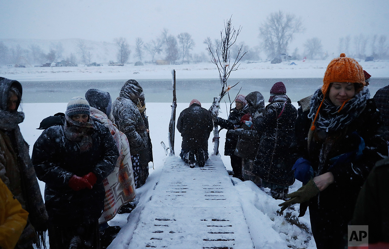 In this Tuesday, Nov. 29, 2016 photo, a person prays along the Cannonball River during a Native American water ceremony at the Oceti Sakowin camp where people have gathered to protest the Dakota Access oil pipeline in Cannon Ball, N.D. So far, those fighting the Dakota Access pipeline have shrugged off the heavy snow, icy winds and frigid temperatures that have swirled around their large encampment on the North Dakota grasslands. (AP Photo/David Goldman)