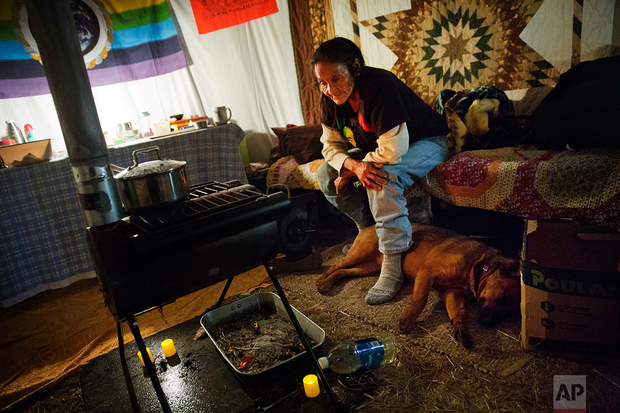 "In this Tuesday, Nov. 29, 2016 photo, Grandma Redfeather of the Sioux Native American tribe sits by the wood stove in her yurt at the Oceti Sakowin camp where people have gathered to protest the Dakota Access oil pipeline in Cannon Ball, N.D. ""I love it because I get to live my traditional way of life,"" said Redfeather of living at the camp. ""To see all the different tribal nations living together as a community, I would have loved my grandpa to see that."" (AP Photo/David Goldman)"