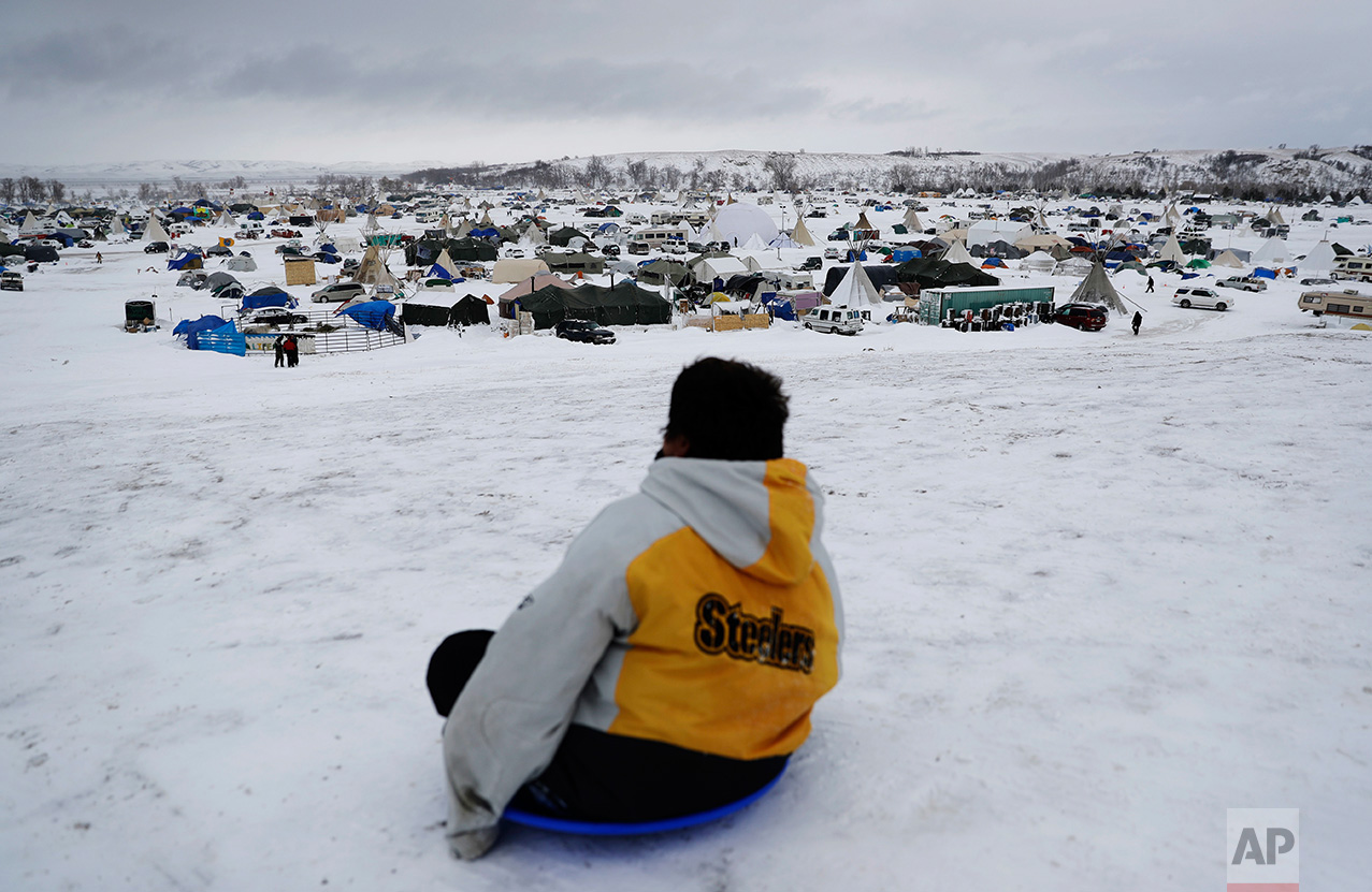 In this Tuesday, Nov. 29, 2016 photo, the Oceti Sakowin camp where people have gathered to protest the Dakota Access oil pipeline stands in the background as a boy sleds down a hill in Cannon Ball, N.D. The government has ordered protesters to leave federal land by Monday, but they insist they will stay for as long it takes to divert the $3.8 billion pipeline. (AP Photo/David Goldman)