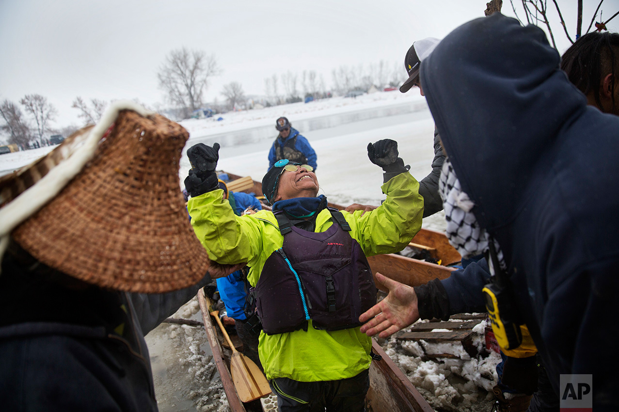 In this Thursday, Dec. 1, 2016 photo, Patty Sam Porter of Colville, Wash., and a member of the Colville Native American tribe, celebrates upon reaching shore by canoe at the Oceti Sakowin camp where people have gathered to protest the Dakota Access oil pipeline in Cannon Ball, N.D. Porter traveled from Montana with fellow tribal members on canoe for 10 days down the Missouri river to reach the camp. (AP Photo/David Goldman)
