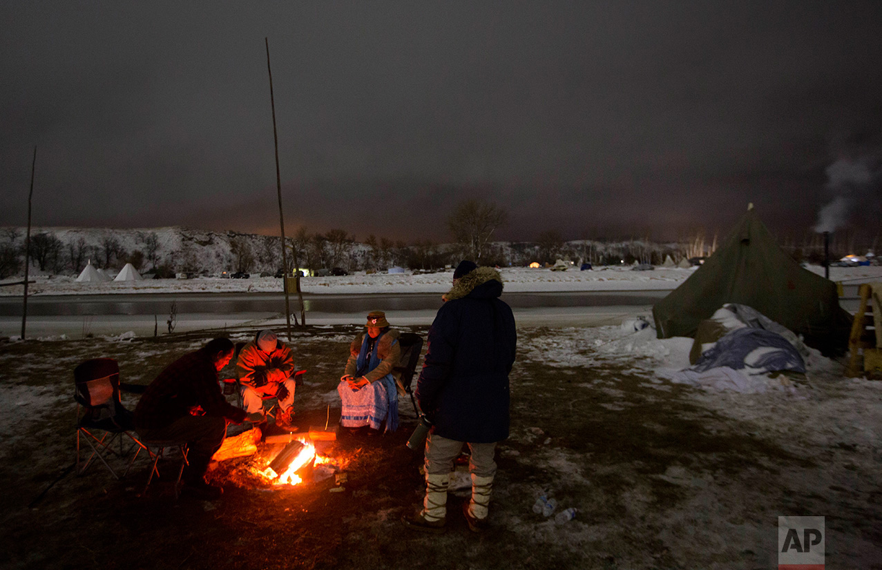 In this Thursday, Dec. 1, 2016 photo, campers sit around a fire along the Cannonball river at the Oceti Sakowin camp where people have gathered to protest the Dakota Access pipeline in Cannon Ball, N.D. So far, those fighting the Dakota Access pipeline have shrugged off the heavy snow, icy winds and frigid temperatures that have swirled around their encampment on the North Dakota grasslands. But if they defy next week's government deadline to abandon the camp, demonstrators know the real deep freeze lies ahead. (AP Photo/David Goldman)