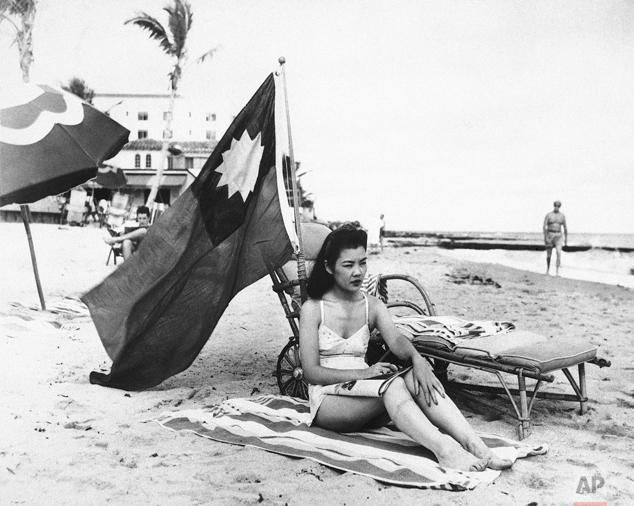 Ruth Lee, hostess at a Miami Chinese restaurant, seen Dec. 15, 1941, doesn't want to be mistaken for Japanese when she sunbathes on her days off, and brings along a Chinese flag.  Miss Lee is actually American-born. (AP Photo)