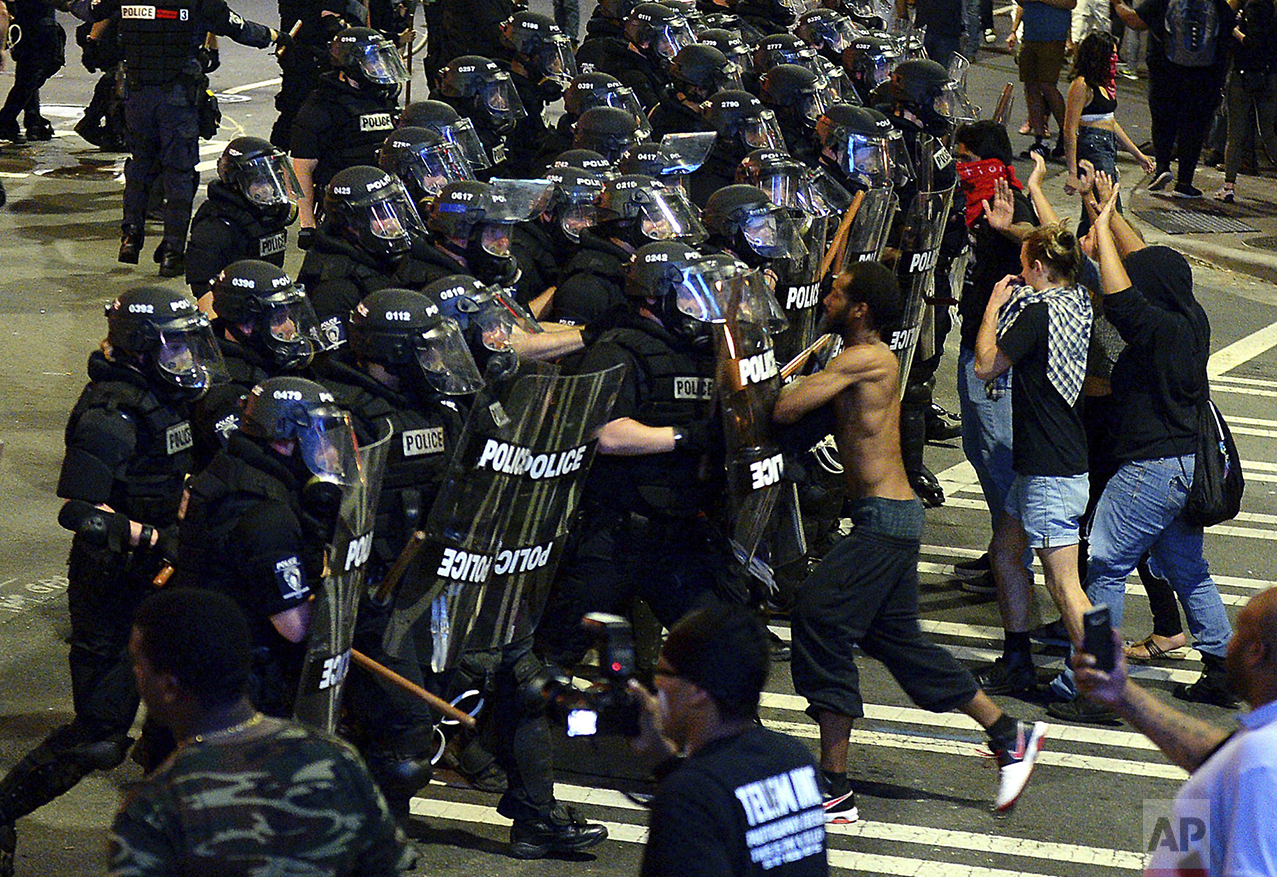 Charlotte-Mecklenburg police officers begin to move protesters down a street in Charlotte, N.C., on Sept. 21, 2016. Authorities in Charlotte tried to quell public anger after a police officer shot a black man, but a dusk prayer vigil turned into a second night of violence, with police firing tear gas at angry protesters and a man being critically wounded by gunfire. North Carolina's governor declared a state of emergency in the city. (Jeff Siner/The Charlotte Observer via AP)