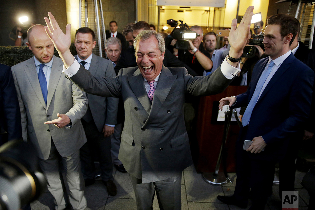 "Nigel Farage, the leader of the UK Independence Party, celebrates and poses for photographers as he leaves a ""Leave.EU"" organization party for the British European Union membership referendum in London on June 24, 2016. (AP Photo/Matt Dunham)"