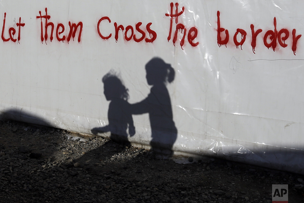 Shadows of children are cast on a tent bearing graffiti at the northern Greek border point of Idomeni, Greece, on May 4, 2016. (AP Photo/Gregorio Borgia)