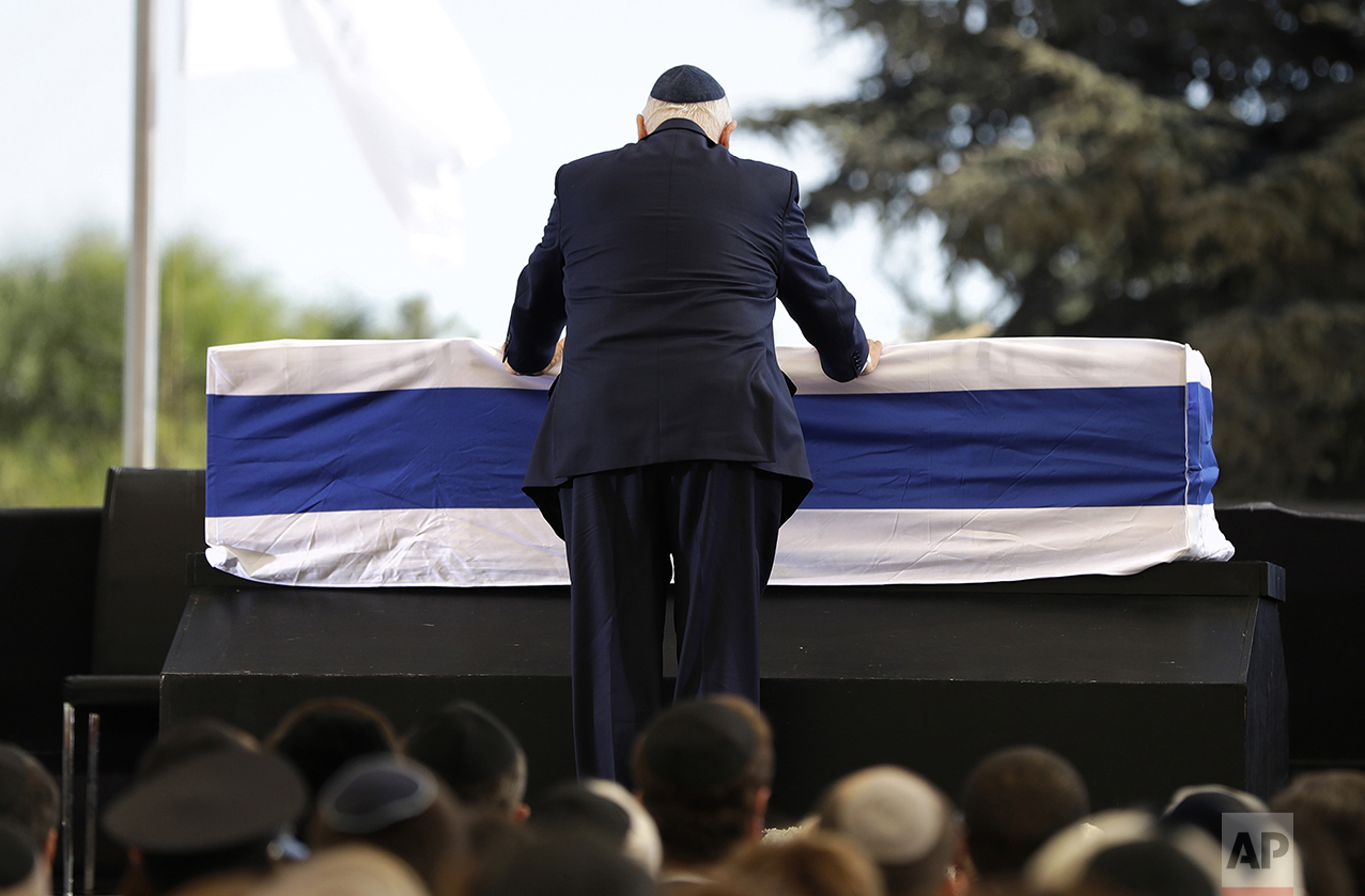 Israeli President Reuven Rivlin places his hands on the casket of former Israeli President Shimon Peres as he takes the stage to speak during a memorial service at Mount Herzl national cemetery in Jerusalem on Sept. 30, 2016. Peres died from complications from a stroke. He was 93. (AP Photo/Carolyn Kaster)