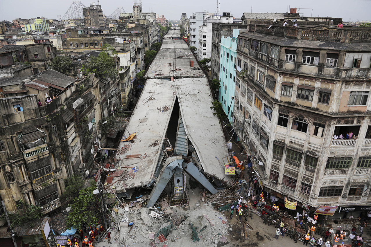 This April 1, 2016 photo shows a partially collapsed overpass in Kolkata, India. The overpass spanned nearly the width of the street and was designed to ease traffic through the densely crowded Bara Bazaar neighborhood in the capital of the east Indian state of West Bengal. About 100 meters (300 feet) of the overpass fell, while other sections remained standing. (AP Photo/Bikas Das)