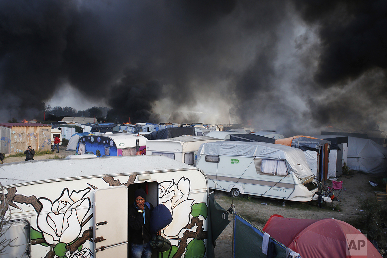 "A man carrying his belongings reacts as he leaves a caravan, as smoke and flames rise from the tents after fires were started in the makeshift migrant camp known as ""the jungle"" near Calais, northern France, on Oct. 26, 2016. (AP Photo/Thibault Camus)"