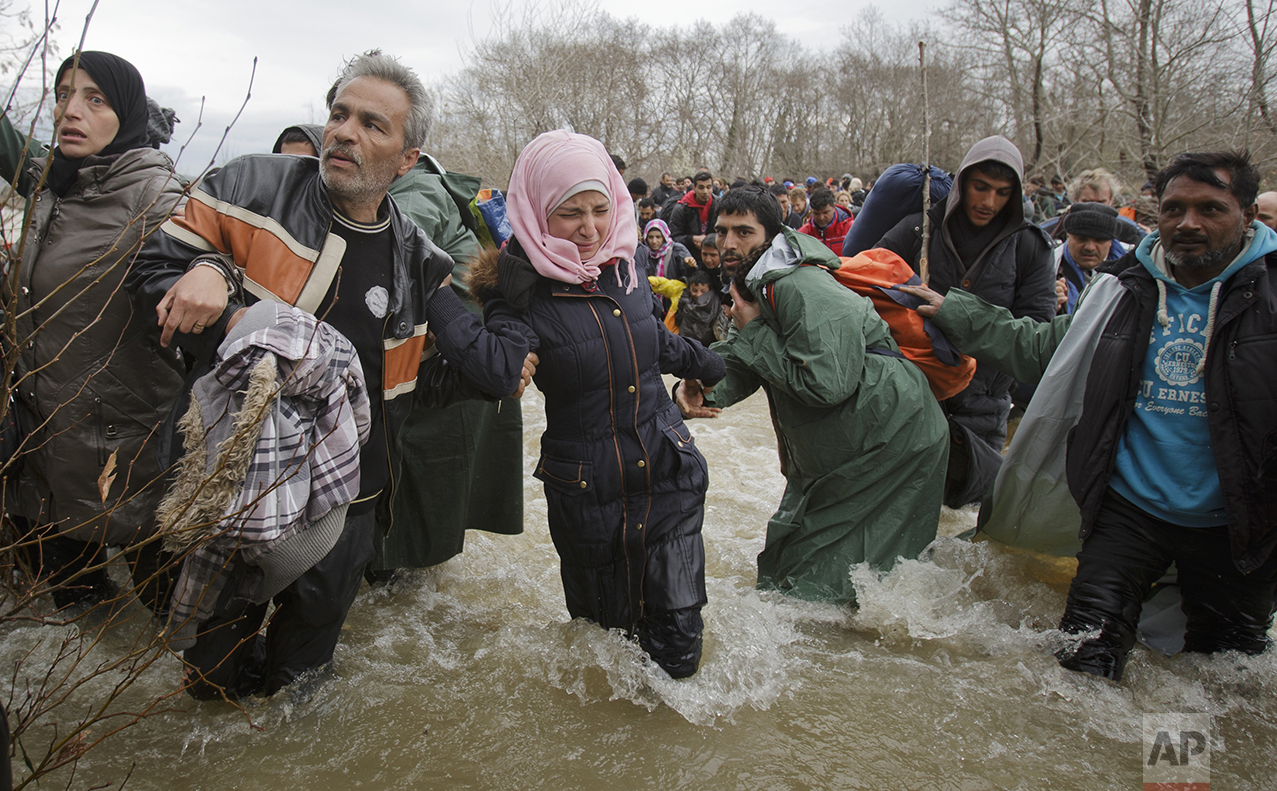 A woman cries as she crosses the river along with other migrants, north of Idomeni, Greece, attempting to reach Macedonia on a route that would bypass the border fence, on March 14, 2016. (AP Photo/Vadim Ghirda)