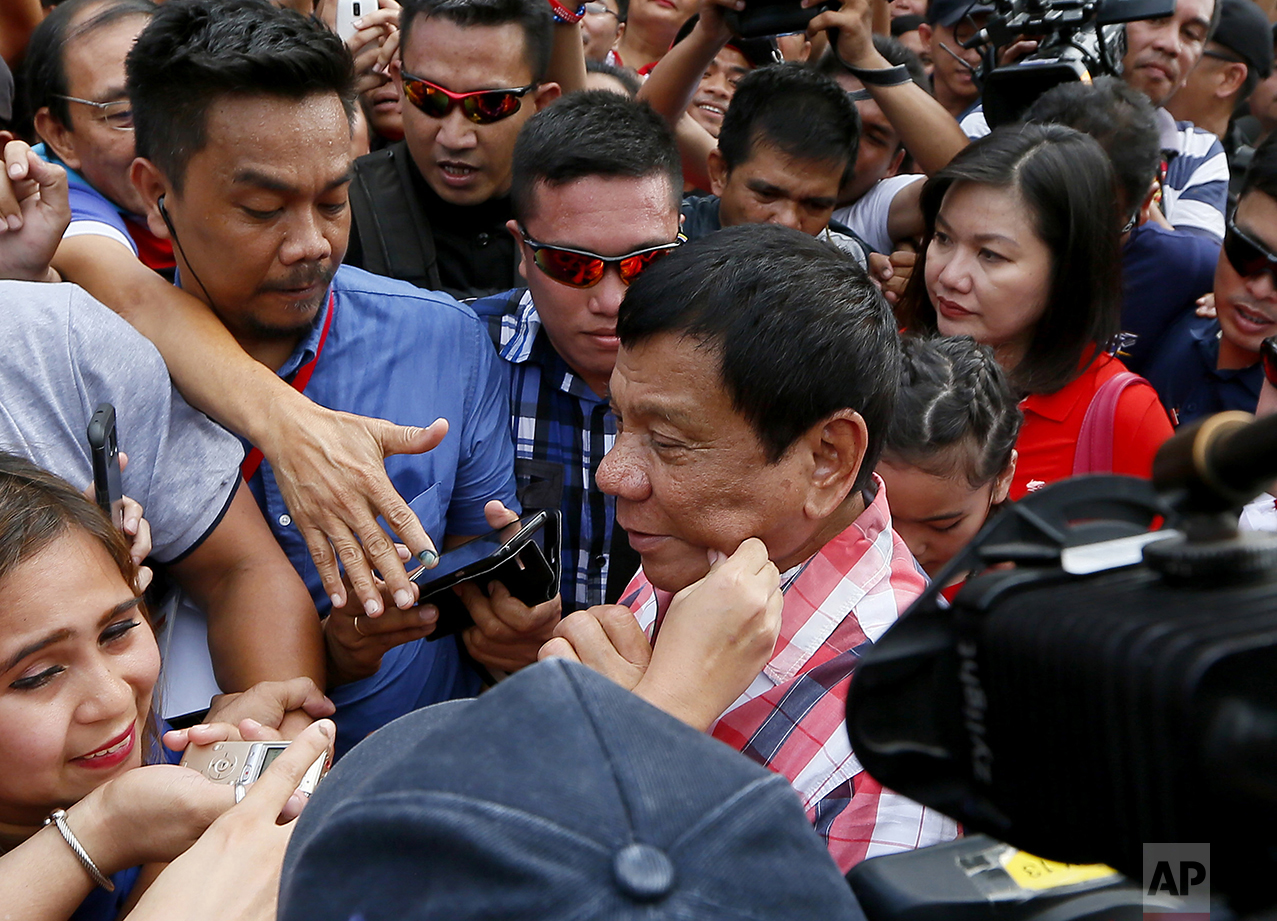 A supporter pinches the cheek of front-running presidential candidate Mayor Rodrigo Duterte as he leaves Daniel R. Aguinaldo National High School at Matina district, his hometown, after voting in Davao city in southern Philippines on May 9, 2016. (AP Photo/Bullit Marquez)