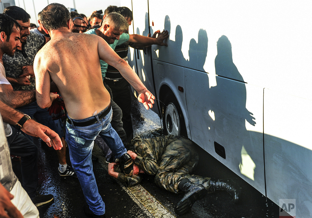 People kick and beat a Turkish soldier that participated in an attempted coup, on Istanbul's Bosporus Bridge, on July 16, 2016. Turkish President Recep Tayyip Erdogan told the nation that his government was working to crush a coup attempt after a night of explosions, air battles and gunfire across the capital that left dozens dead and scores wounded. (AP Photo/Selcuk Samiloglu)