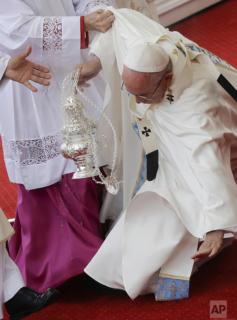 Pope Francis is helped by Vatican Master of Ceremonies, Mons. Guido Marini as he stumbles on the altar while celebrating a mass in Czestochowa, Poland, on July 28, 2016. (AP Photo/Gregorio Borgia)