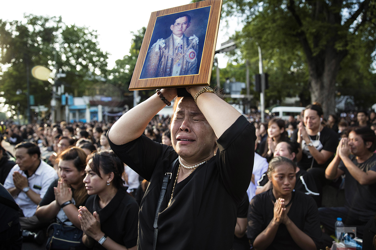 A Thai woman cries as she holds a picture of the late King Bhumibol Adulyadej while others clasp their hands to pay last respects to a passing van carrying the body of their king outside the Grand Palace in Bangkok, Thailand, on Oct. 14, 2016. Bhumibol, the world's longest reigning monarch, died at the age of 88. (AP Photo/Wason Wanichakorn)