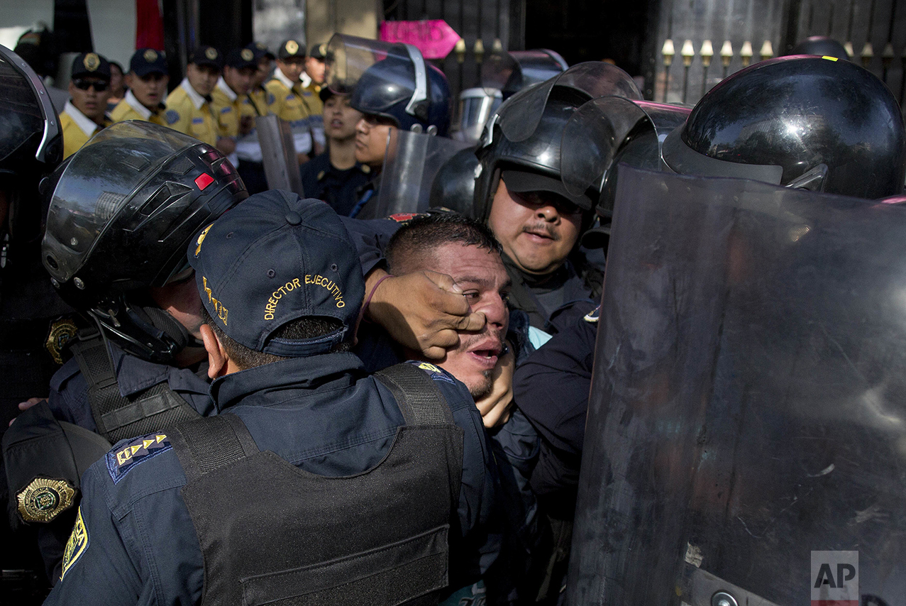Police detain a taxi driver who, along with other cabbies, blocked a main road to protest the one day per week driving restriction in Mexico City on April 13, 2016. Under new regulations imposed after the capital experienced its worst air-quality crisis in over a decade, 40 percent of cars were ordered temporarily off the road. (AP Photo/Eduardo Verdugo)